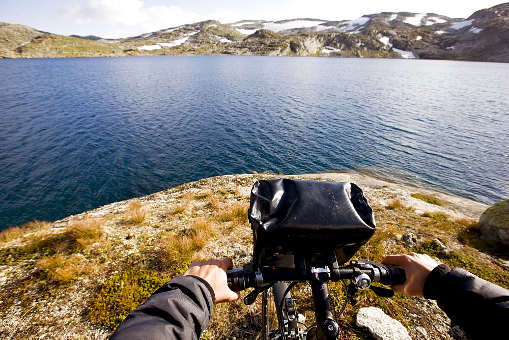 Cyclist at a lake on the Rallarvegen in late summer, Hardangervidda national park, Hordaland, South of Norway, Scandinavia, Europe