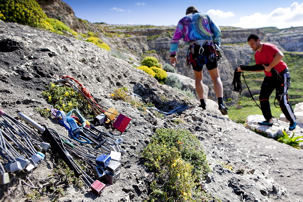Two men preparing for climbing, climbing equipement in the foreground, Inland Sea, Dwerja Bay, Gozo, Malta, Europe
