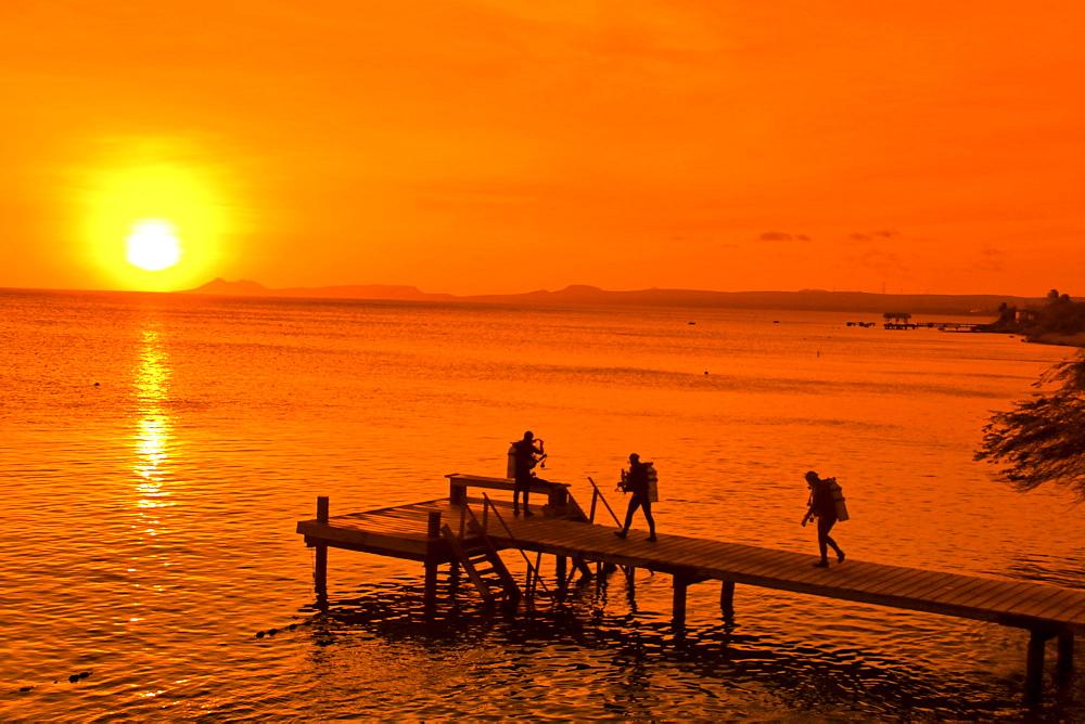 West Indies, Bonaire, sunset, pier, diver near Captain Don s Habitat, diving resort