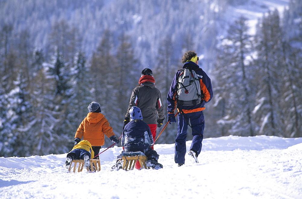 Family taking a walk in the ski resort of Motta Naluns above Scuol, Lower Engadine, Engadine, Switzerland