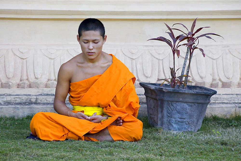 Buddhistic monk sitting in front of monastery Vat Pa Phonphao, Luang Prabang, Laos