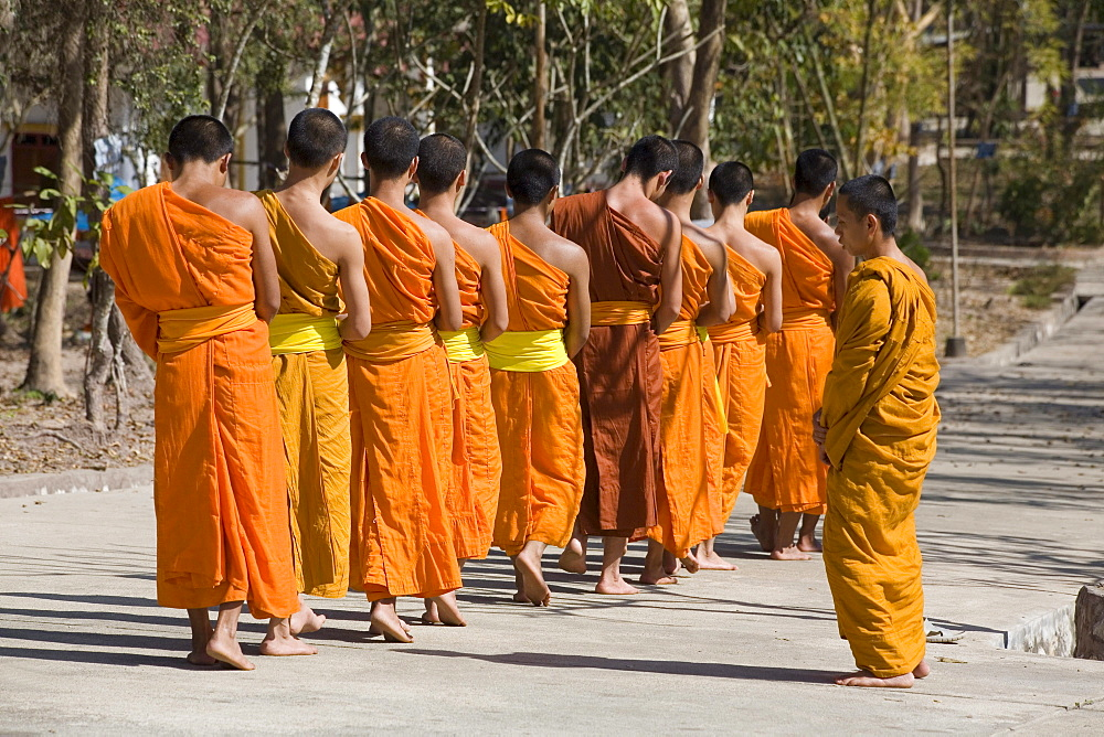 Buddhistic monks walking on a street in front of the monastery Vat Pa Phonphao, Luang Prabang, Laos
