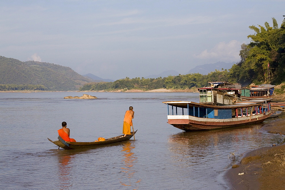 Two young buddhistic monks in a boat on the river Mekong, Luang Prabang, Laos