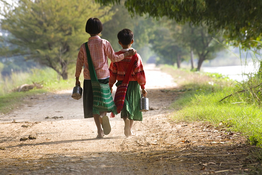 Two young school girls from behind walking on Inwa island ( Ava ) at Ayeyarwady River near Amarapura, Myanmar, Burma