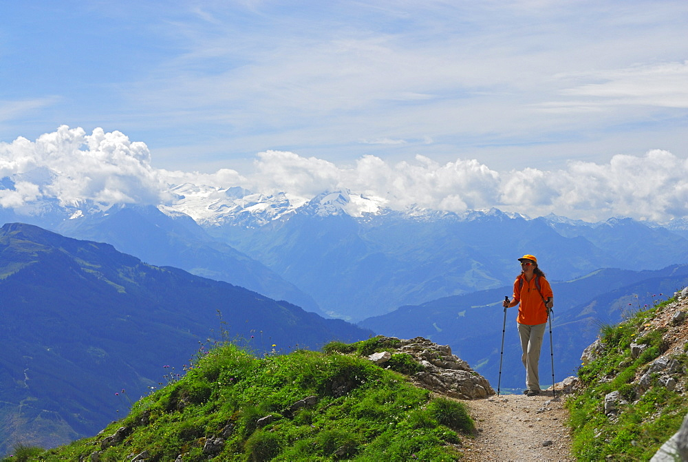 young woman on trail above valley of Maria Alm with view to Hohe Tauern range, Steinernes Meer range, Berchtesgaden range, Salzburg, Austria