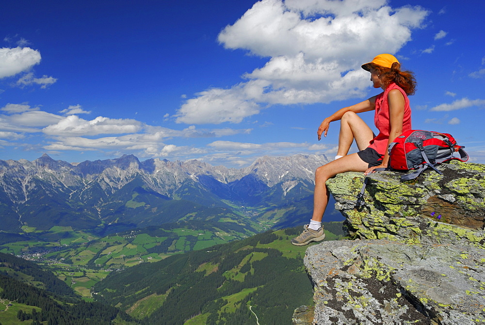 young woman sitting on rock with Steinernes Meer range and Hochkoenig in Berchtesgaden range in background, Hundstein, Salzburger Schieferalpen range, Salzburg, Austria