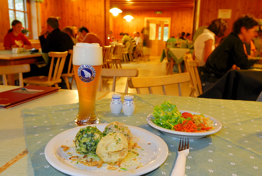 laid table with one portion of Tyrolean Knoedel, Spinatknoedel, Kasknoedel and Speckknoedel, mixed salad and weissbier, guests at tables out of focus in background, hut Franz-Senn-Huette, Stubaier Alpen range, Stubai, Tyrol, Austria