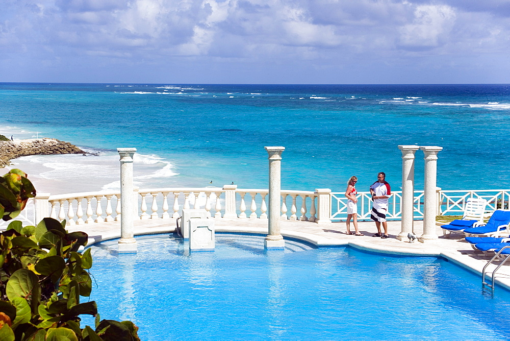 Vacationer at swimming pool of the Crane Hotel, Atlantic Ocean in background, Barbados, Caribbean