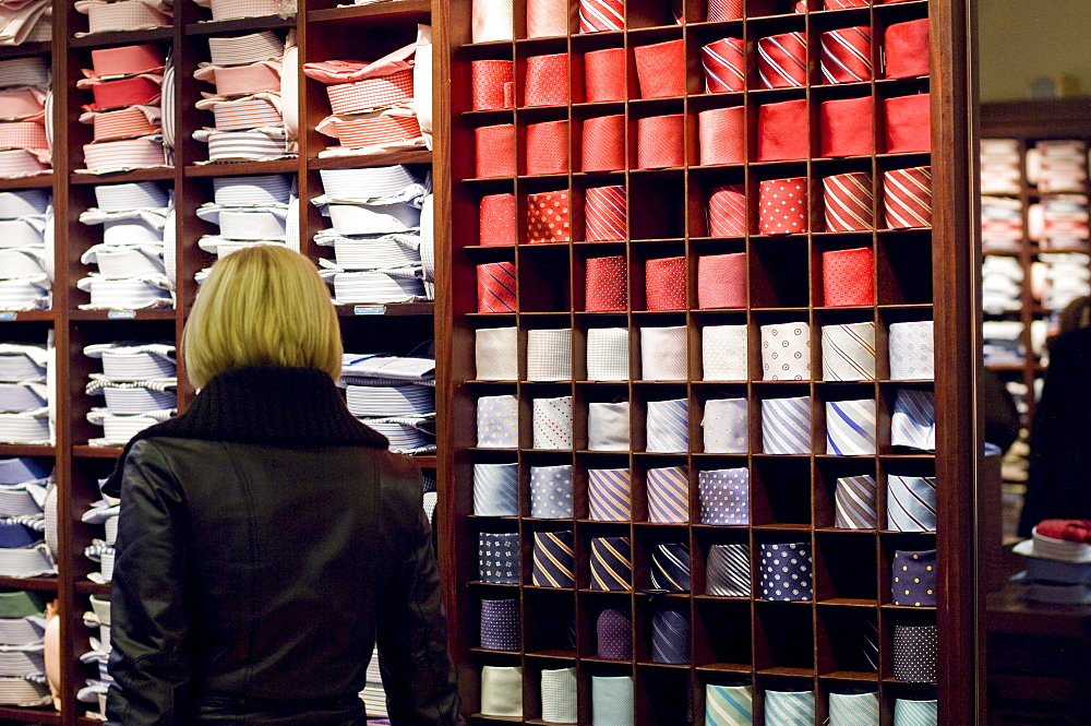 Woman in a mens clothes shop, looking at shirts and ties, Ingolstadt, Bavaria, Germany