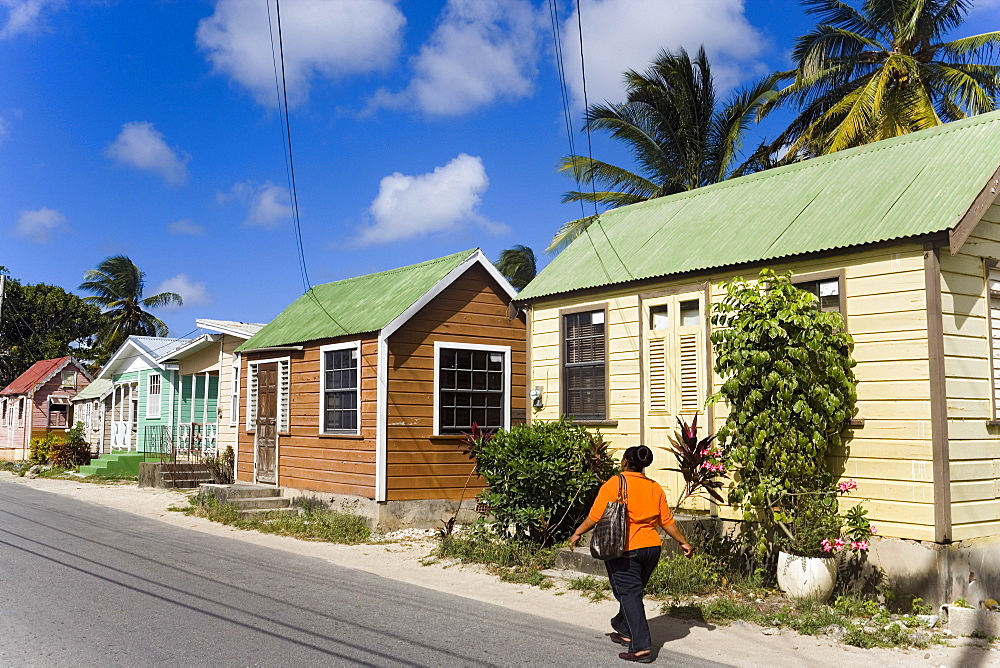 Woman walking along Chattel Houses, Six Men's Bay, Barbados, Caribbean
