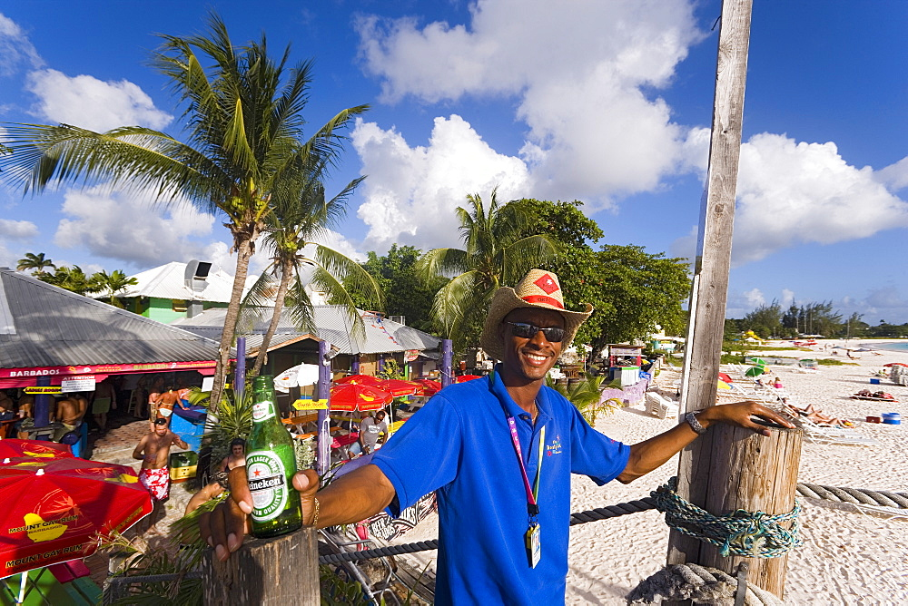 Man smiling at camera, the Boatyard beach bar in background, Bridgetown, Barbados, Caribbean