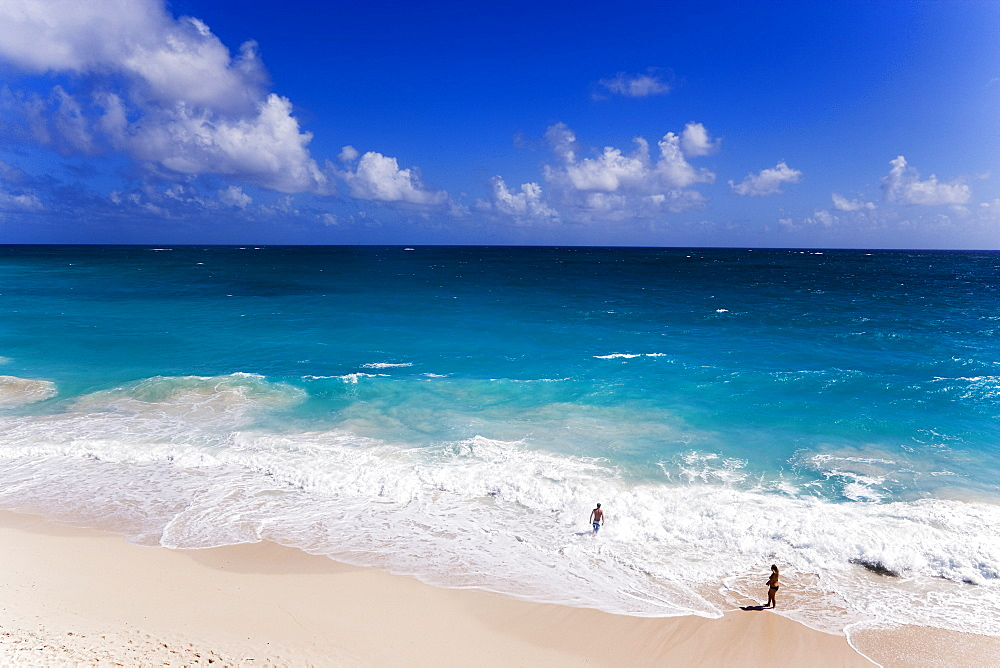 Couple standing in spray of Atlantic Ocean at Bottom Bay, St. Philip, Barbados, Caribbean
