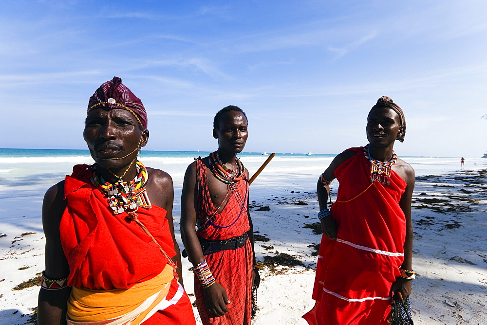 Three plastic Massai wearing traditional clothing at Diani Beach, Coast, Kenya