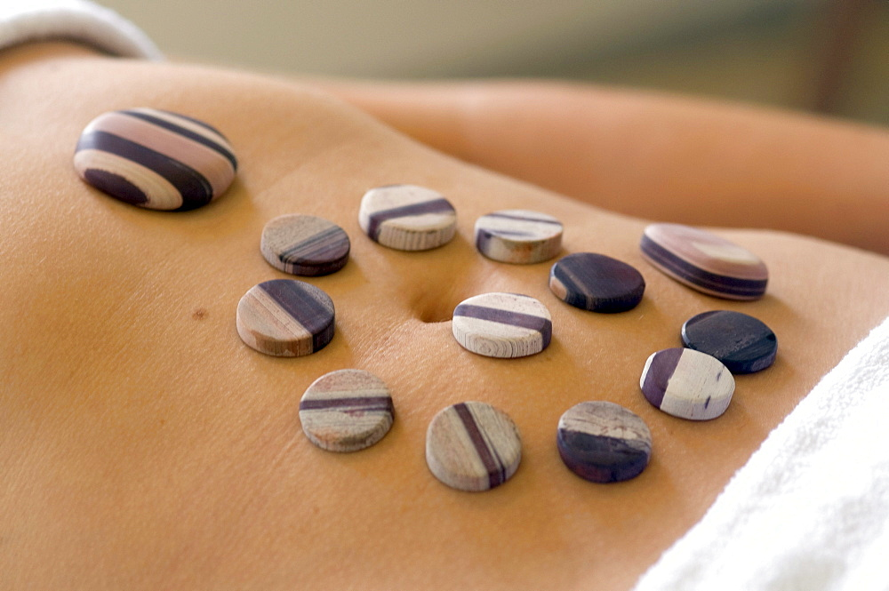 Spa treatment, warm stones lying on the nude belly, Kangaroo Island, South Australia, Australia