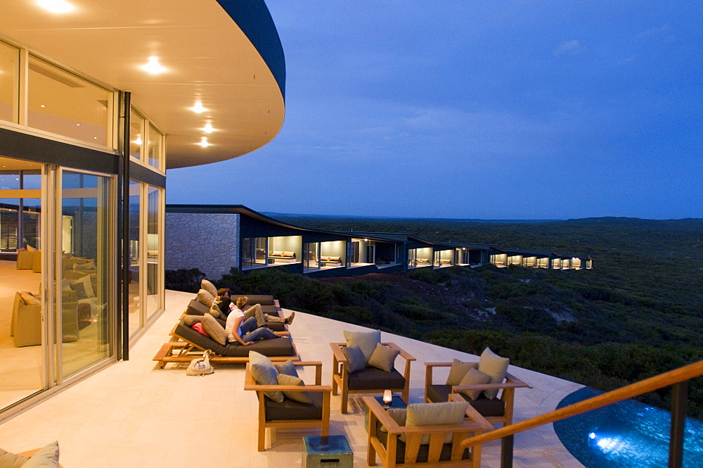 People on the illuminated terrace in front of the rooms of Southern Ocean Lodge, Kangaroo Island, South Australia, Australia