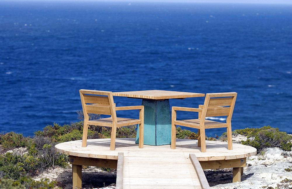 Chairs and a table on a terrace high above the ocean, Kangaroo Island, South Australia, Australia