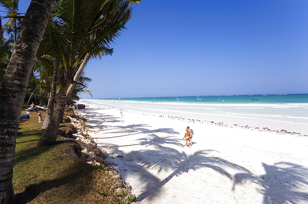 Women walking along Diani Beach, Coast, Kenya