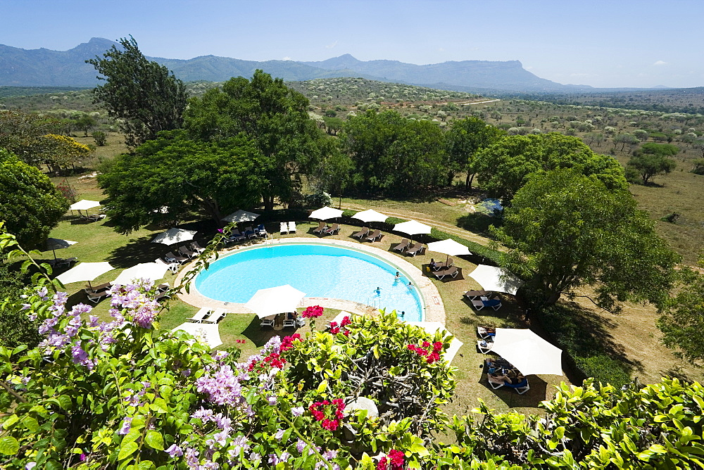 View over swimming pool of Taita Hills Lodge, Taita hills in background, Coast, Kenya
