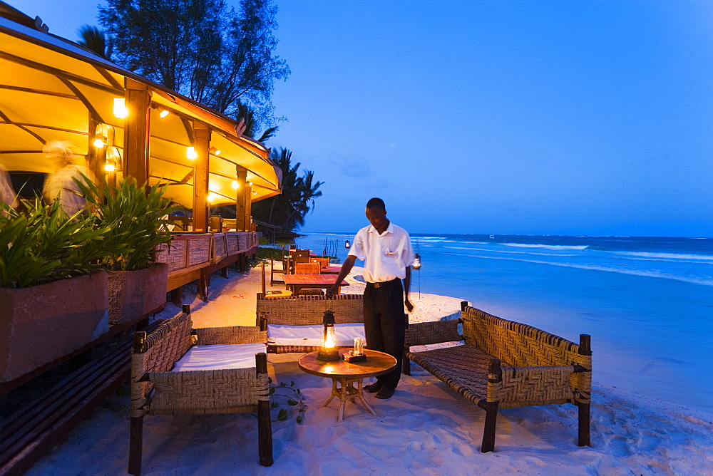 Waiter arranging lanterns, The Sands, at Nomad, Diani Beach, Kenya
