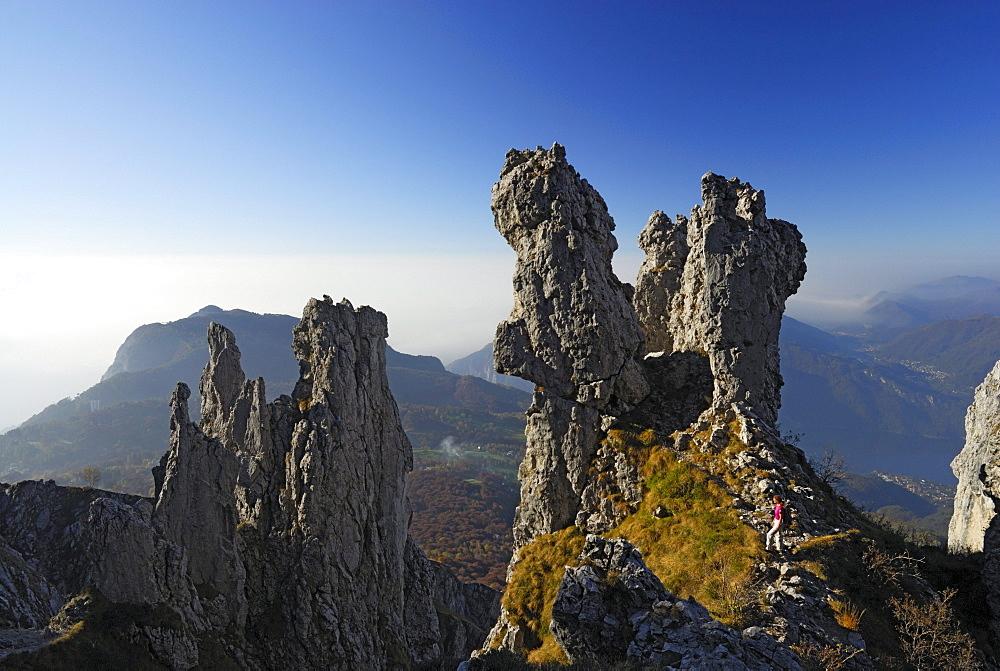 Woman hiking between pinnacles of Grigne, Bergamo Alps, Como, Lombardy, Italy