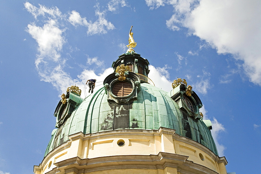 industrial climber working on dome of Charlottenburg Palace, Berlin, Germany