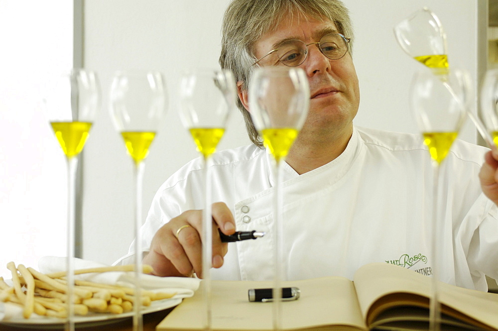 A cook tasting olive oil, Restaurant zur Rose, South Tyrol, Italy, Europe