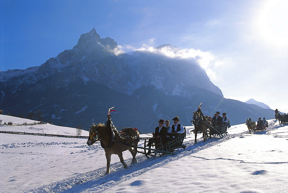 People wearing traditional costumes driving in sleighs through sunlit winter landscape, Sciliar, South Tyrol, Italy, Europe