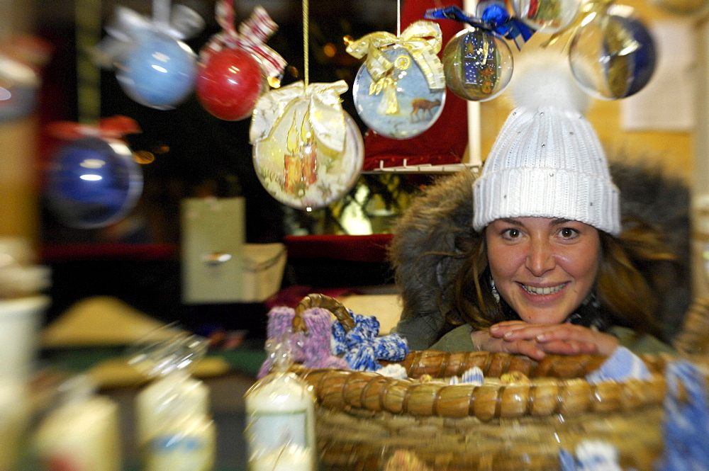 Smiling woman selling baubles at a sales booth at christmas market, Kastelruth, Valle Isarco, South Tyrol, Italy, Europe