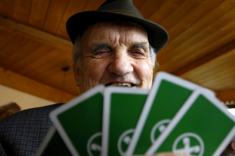 The face of an old man above playing cards, South Tyrol, Italy, Europe