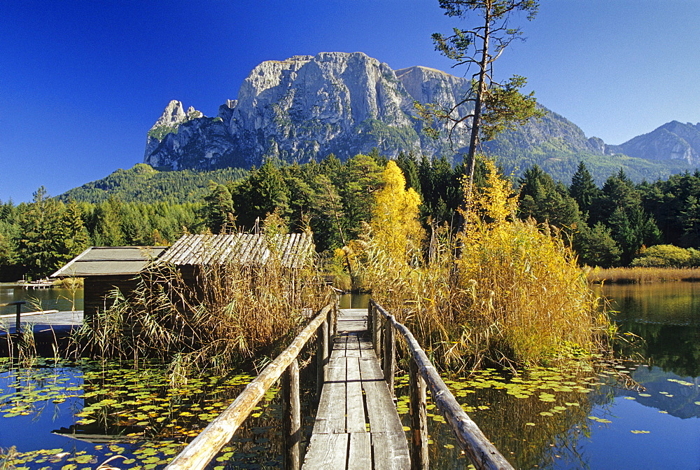 Wooden jetty on the lake, Lago di Fie, view to Monte Sciliar, Dolomite Alps, South Tyrol, Italy