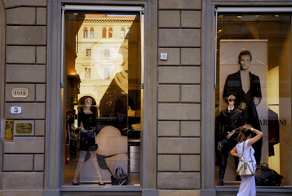 A woman in front of the shop window of the Designer Shop by Armani, Florence, Tuscany, Italy, Europe