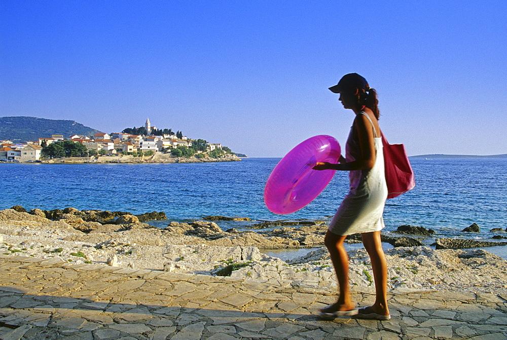 A woman on the seaside promenade of Primosten, Croatian Adriatic Sea, Dalmatia, Croatia, Europe