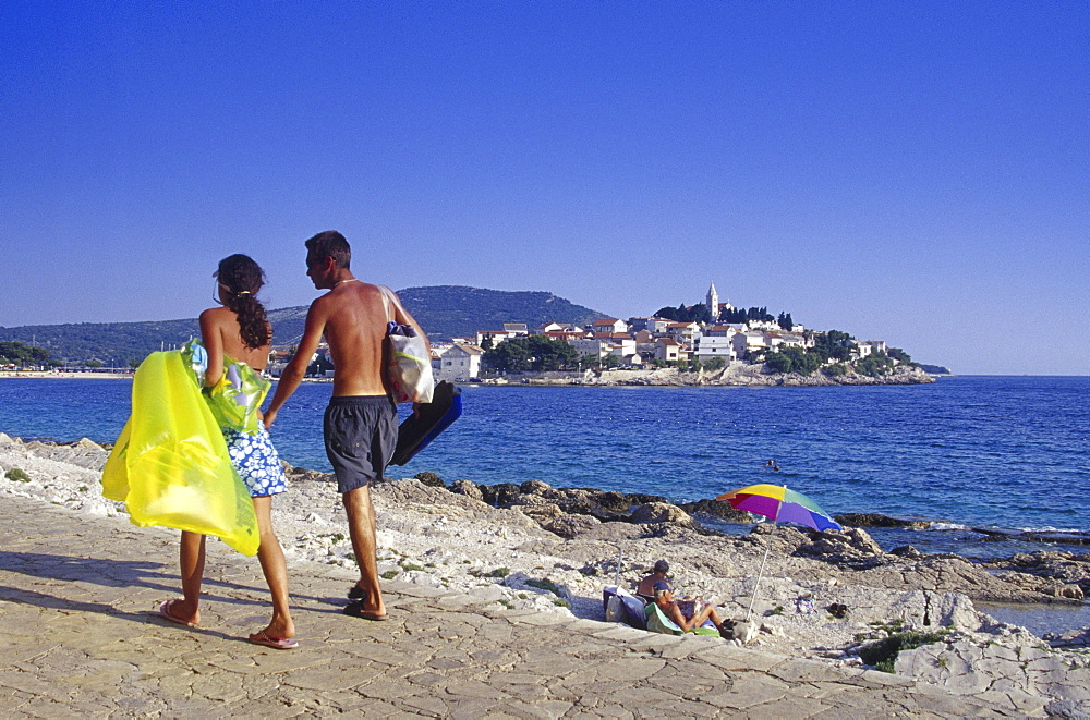 People on the seaside promenade under blue sky, Primosten, Croatian Adriatic Sea, Dalmatia, Croatia, Europe