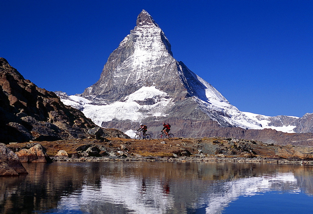 Mountain bikers at a lake in front of the Matterhorn mountain, Switzerland, Europe