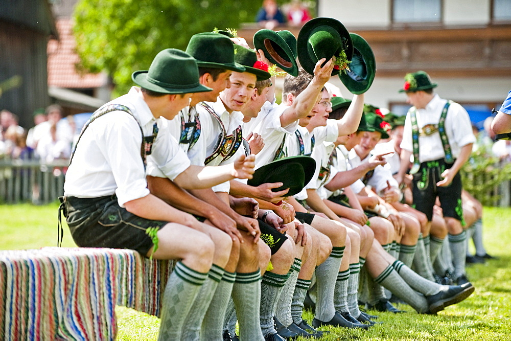 Young men wearing traditional costumes sitting side by side, May Running, Upper Bavaria, Germany