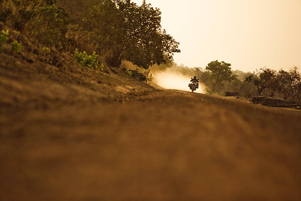 Man on motorcycle riding on a dirt road in the evening, Mali, Africa