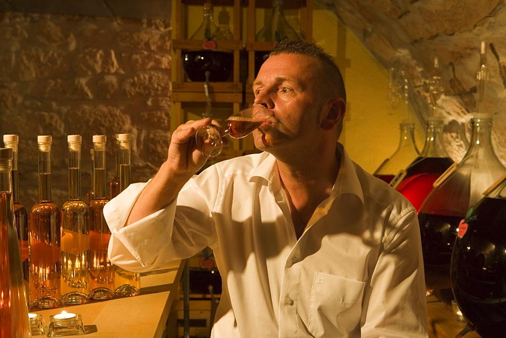 Proprietor Juergen H. Krenzer testing apple sherry in the Apple Wine and Sherry Cellar at Rhoener Schau-Kelterei, Gasthof Zur Krone, Das Rhoenschaf Hotel, Ehrenberg, Seiferts, Rhoen, Hesse, Germany