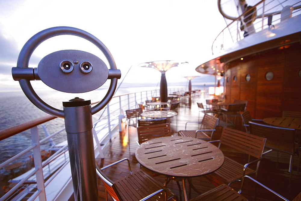 Binoculars, tables and chairs on AIDA Bella cruiser in the evening, Mediterranean Sea