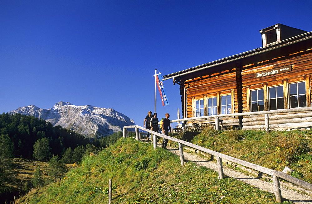 alpine hut Gotzenalm with hikers, Steinernes Meer in background, Berchtesgaden range, Berchtesgaden, Upper Bavaria, Bavaria, Germany