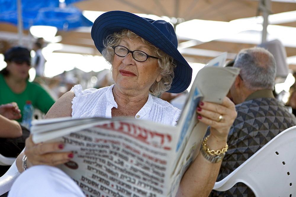 Old woman reading newspaper, Gordon Beach, Tel Aviv, Israel, Middle East