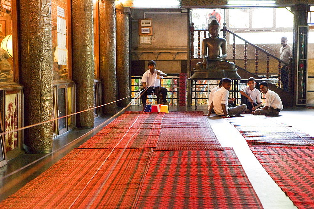 Men preparing colored blessing ribbons at the Gangaramaya temple, Colombo, Sri Lanka, Asia