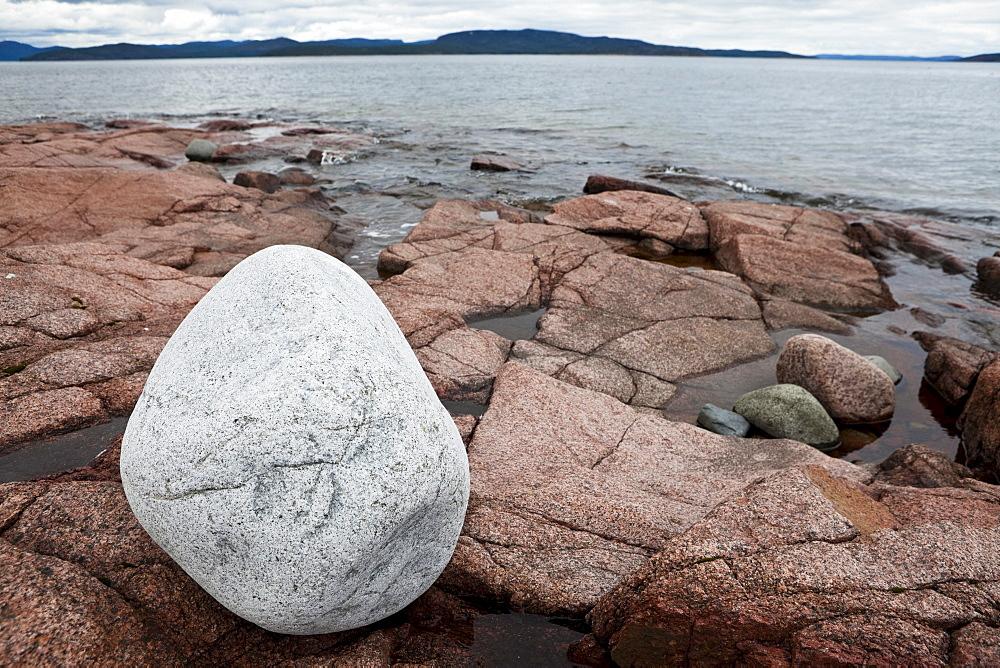 White boulder on red granit rocks at the Hoega Kusten, bay of Storsands Havsbad, Vaesternorrland, Sweden, Europe