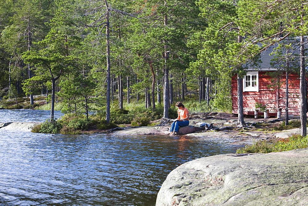 Woman sitting in front of a small cottage at the lake Taernaettvatten, national park Skuleskogen, Hoega Kusten, Vaesternorrland, Sweden, Europe