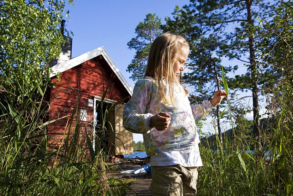 Girl in front of small cottage at the lake Taernaettvatten, national park Skuleskogen, Hoega Kusten, Vaesternorrland, Sweden, Europe