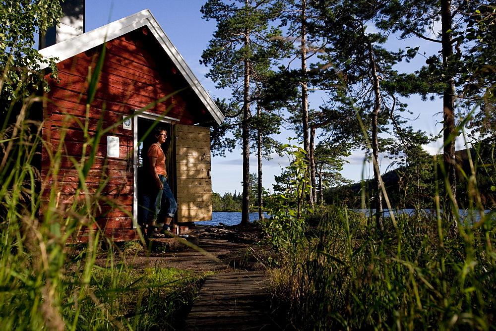 Woman and small cottage at the lake Taernaettvatten, nationalpark Skuleskogen, Hoega Kusten, Vaesternorrland, Sweden, Europe