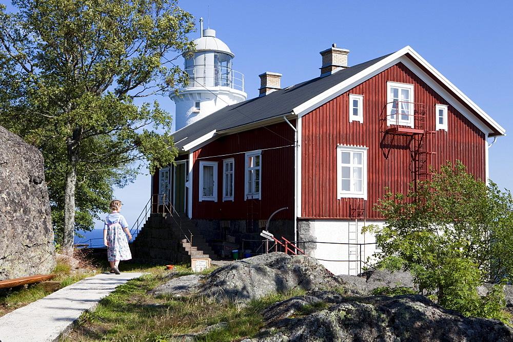 Wooden house and lighthouse Hoegbonden under blue sky, Hoega Kusten, Vaesternorrland, Sweden, Europe