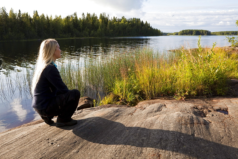 A woman looking over a lake, Vaesterbotten, Sweden, Europe