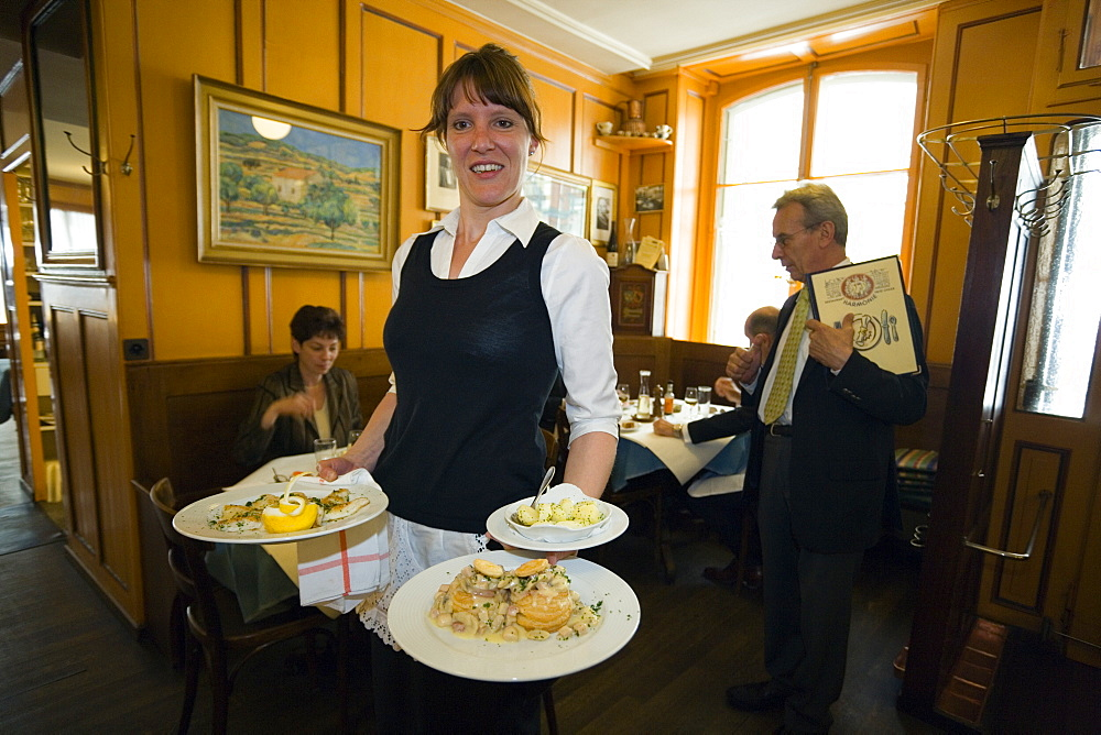 A waitress carrying traditional food, Restaurant Harmonie, Old City of Berne, Berne, Switzerland