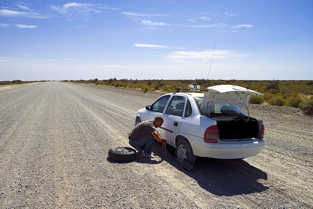 Taxi with flat tire on gravel road, Peninsula Valdes, Chubut, Patagonia, Argentina, South America, America
