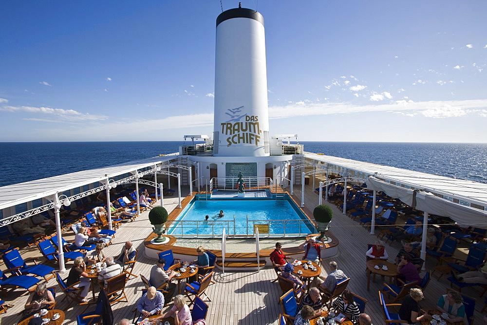 Passengers enjoying coffee and cake on pool deck aboard cruiseship MS Deutschland (Deilmann Cruises), South Atlantic Ocean, South America, America